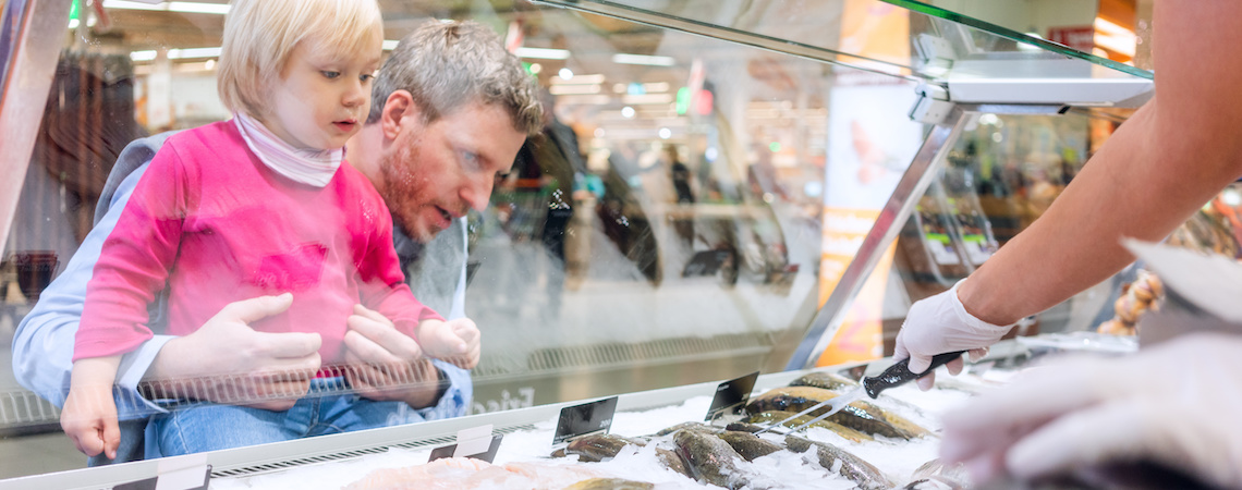Parent and child looking at the fishmonger product display